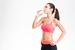 Beautiful young fitness woman drinking water from plastic bottle Royalty Free Stock Image