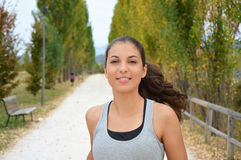 Beautiful young fitness woman running in the park. Smiling girl training outdoors Stock Photo
