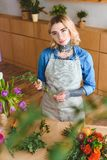 Beautiful young florist in apron and eyeglasses arranging flowers and looking. At camera royalty free stock photography