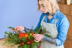 Beautiful young florist in eyeglasses arranging. Flower bouquet stock photos
