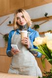 Beautiful young florist holding coffee to go and smartphone and looking at camera in flower. Shop stock photos