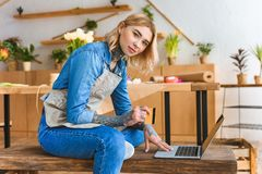 Beautiful young florist holding credit card and looking at camera while using laptop in flower. Shop stock photos