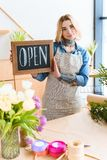 Beautiful young florist holding open sign and looking at camera. In flower shop royalty free stock image