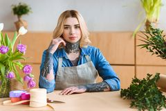 Beautiful young florist sitting at workplace and looking at camera. In flower shop royalty free stock images