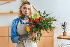 Beautiful young florist with tattoos holding flower bouquet and looking. At camera royalty free stock images
