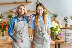 Beautiful young florists in aprons smiling at camera. In flower shop royalty free stock photos