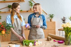 Beautiful young florists working together and smiling each other. In flower shop royalty free stock photos