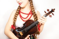A beautiful young folk woman holding a violin. A beautiful young woman wearing a traditional folk costume with long blonde hair tresses, ribbons and red lipstick Royalty Free Stock Images