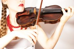 Beautiful young folk woman playing violin. A beautiful young woman wearing a traditional folk costume with long blonde hair tresses, ribbons and red lipstick Stock Photography