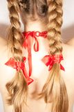A beautiful young folk woman presents her long tresses. A beautiful young woman with long blonde hair tresses and red ribbons Royalty Free Stock Photography