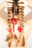 A beautiful young folk woman presents her long tresses. A beautiful young woman with long blonde hair tresses and red ribbons Stock Photography