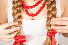 A beautiful young folk woman presents her long tresses. A beautiful young woman wearing a traditional folk costume with long blonde hair tresses and red ribbons Stock Photos