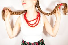 A beautiful young folk woman presents her long tresses. A beautiful young woman wearing a traditional folk costume with long blonde hair tresses, ribbons and red Stock Photos