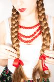 A beautiful young folk woman presents her long tresses. A beautiful young woman wearing a traditional folk costume with long blonde hair tresses, ribbons and red Royalty Free Stock Photography