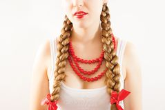Beautiful young folk woman. A beautiful young woman wearing a traditional folk costume with long blonde hair tresses, ribbons and red lipstick Royalty Free Stock Photography