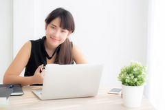 Beautiful young freelance asian woman smiling working and typing on laptop computer at desk office with professional. Girl using notebook checking email or stock images
