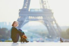 Beautiful young French woman near the Eiffel tower in Paris. Beautiful young French woman with bunch of colorful autumn leaves near the Eiffel tower in Paris on Royalty Free Stock Image