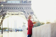 Beautiful young French woman near the Eiffel tower in Paris. Beautiful young French woman drinking coffee near the Eiffel tower in Paris on a fall or spring day Royalty Free Stock Photography