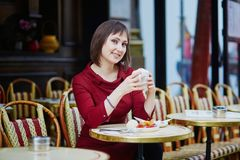Woman drinking coffee in Parisian outdoor cafe Royalty Free Stock Photo