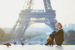 Beautiful young French woman near the Eiffel tower in Paris Stock Photos