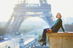 Beautiful young French woman near the Eiffel tower in Paris Royalty Free Stock Images