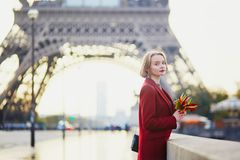 Beautiful young French woman near the Eiffel tower in Paris Stock Images