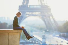 Beautiful young French woman near the Eiffel tower in Paris. Beautiful young French woman with bunch of colorful autumn leaves near the Eiffel tower in Paris on Royalty Free Stock Photography