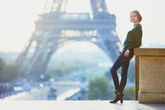 Beautiful young French woman near the Eiffel tower in Paris. Beautiful young French woman with bunch of colorful autumn leaves near the Eiffel tower in Paris on stock photos