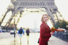 Beautiful young French woman near the Eiffel tower in Paris. Beautiful young French woman drinking coffee near the Eiffel tower in Paris on a fall or spring day Stock Photo