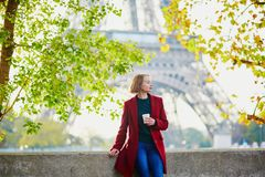 Beautiful young French woman near the Eiffel tower in Paris royalty free stock image