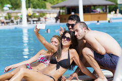 Beautiful young friends having fun making selfie on the pool Royalty Free Stock Photography