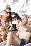 Beautiful young friends laughing and making selfie on the pool royalty free stock photos