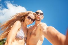 Beautiful young funny couple doing selfie on the shore of the tr stock image