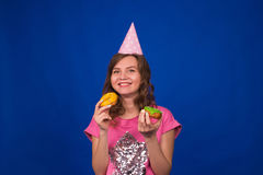 Beautiful young funny girl with donuts on blue background. Unhealthy diet, junk food, party and celebration concept Royalty Free Stock Images