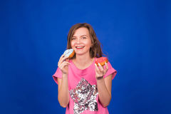 Beautiful young funny girl with donuts on blue background. Unhealthy diet, junk food, party and celebration concept.  Stock Image