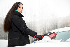 Beautiful young funny woman removing snow from her car Stock Photography