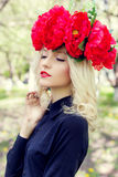 Beautiful young gentle elegant young blond woman with a red crown of peony in a black blouse walks in the lush apple orchard Royalty Free Stock Images
