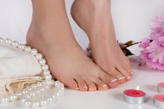 Girl bare feet with french pedicure on white towel and decoration candle, pearls and pink flower in beauty studio isolated on whit stock image