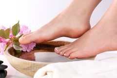 Beautiful female feet in spa studio with french nails polish. Girl legs on wooden bowl with water and pink flowers and towel royalty free stock photo