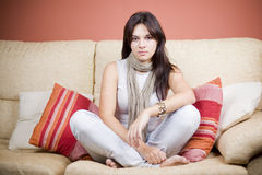 Beautiful young girl. Beautiful girl portrait sitting in the sofa of a living room Royalty Free Stock Photography