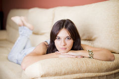 Beautiful young girl. Beautiful girl portrait sitting in the sofa of a living room Stock Photos