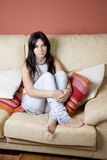 Beautiful young girl. Beautiful girl portrait sitting in the sofa of a living room Stock Photography