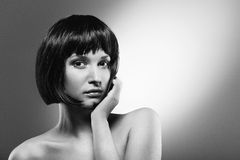 Beautiful young girl. Beautiful serious young girl with black hair in a bob on grey background Stock Images