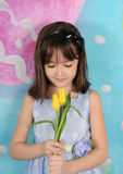 Beautiful young girl admiring tulips at easter Stock Image