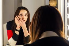 Beautiful young girl is applying makeup near the mirror stock images