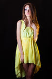 Beautiful young girl with art make-up is removed in the Studio on a black background in a yellow dress Stock Photos