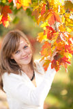 Beautiful young girl with autumn leaves Stock Photography