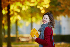 Beautiful young girl in autumn park. With golden foliage on a sunny fall day, holding yellow leaves in her hands stock images