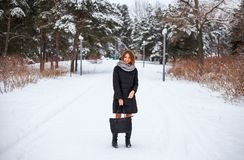 Beautiful young girl with bag in hand in park in winter Stock Photography