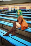 Beautiful young girl with bag posing on bench on football stadium Stock Photos